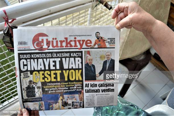 A woman reads Turkiye a Turkish progovernment daily newspaper as the daily runs a headline on its front page that reads 'There is a murder but no...