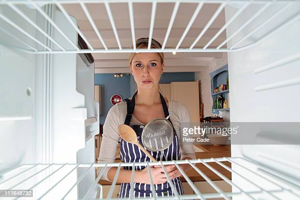 woman ready to cook looking into empty fridge