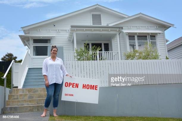 Woman real estate holds an open home sign in front of a traditional bungalow house