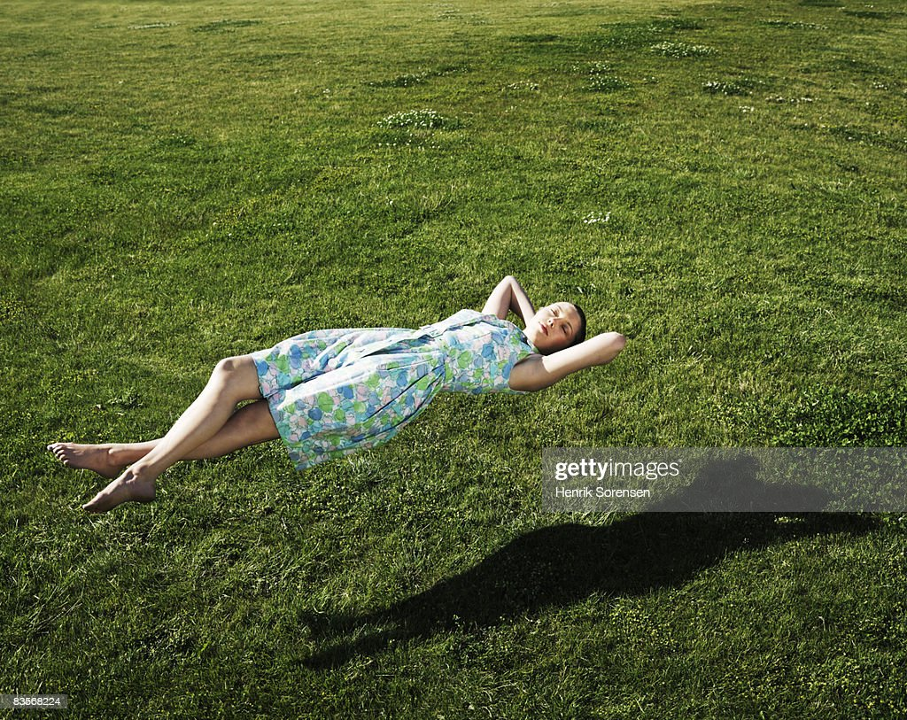 Woman realxing floating above the grass : Stock Photo