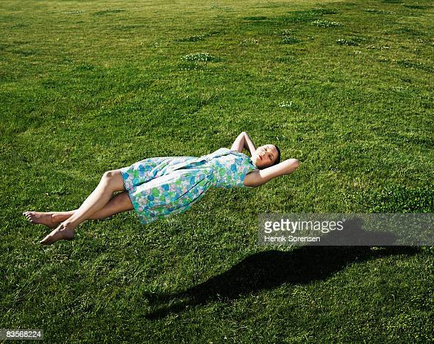 woman realxing floating above the grass - in de lucht zwevend stockfoto's en -beelden