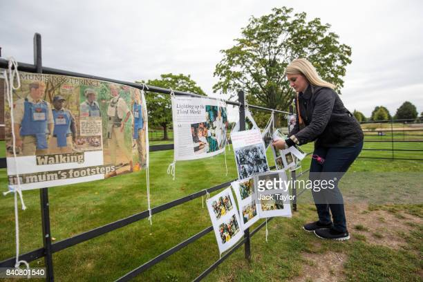 A woman rearranges messages on a fence as floral tributes and photographs sit outside an entrance gate to Kensington Palace ahead of the 20th...