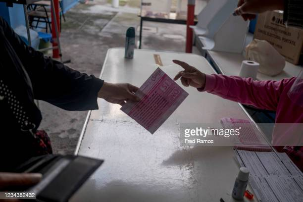 Woman receives a ballot during a referendum to put five former presidents on trial on August 1, 2021 in Mexico City, Mexico. In a proposal carried...