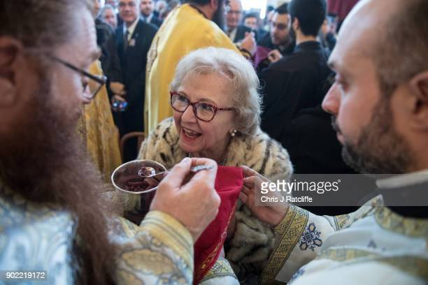 A woman receives a blessing during a traditional Greek Orthodox service at the Church of St Michael the Archangel for the Feast of the Epiphany on...