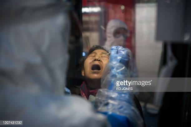 TOPSHOT A woman receives a COVID19 novel coronavirus test swab at a testing booth outside the Yangji hospital in Seoul on March 17 2020 A South...