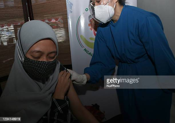 Woman receives a dose of Sinovac vaccine during a mass vaccination for locals at OJK office in Malang City, East Java, Indonesia, on July 24, 2021....