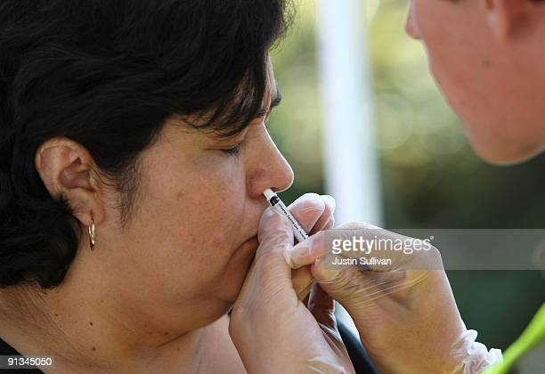 Woman receives a flu vaccine nasal mist as she sits in her car during a drive-thru flu shot clinic October 2, 2009 in Napa, California. The County of...