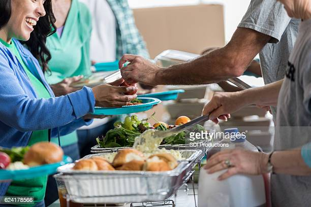 woman receives a healthy meal at soup kitchen - homeless foto e immagini stock