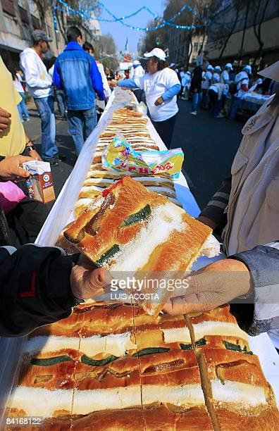 A woman receives a piece of a traditional rosca de Reyes large ringshaped cake baked for Epiphany in Mexico City on January 4 2009 The biggest rosca...