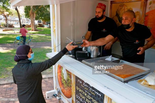 Woman receives a slice of Kunafa, traditional Middle Eastern dessert, after getting vaccinated against coronavirus in the Israeli coastal city of Tel...