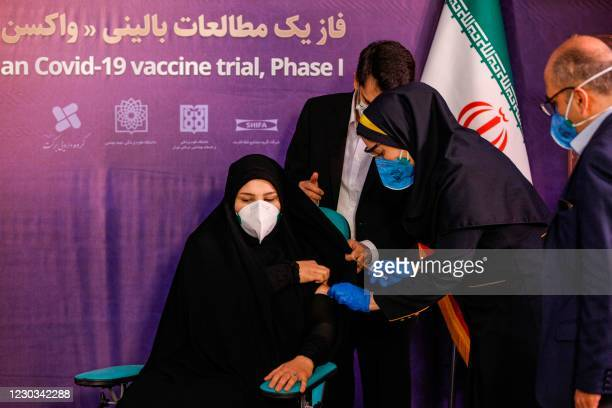 Woman receives an injection during the first trial phase of a locally-made Iranian vaccine for COVID-19 coronavirus disease in Iran's capital Tehran...