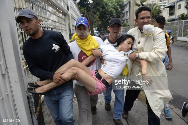 TOPSHOT A woman receives attention during a march against President Nicolas Maduro in Caracas on May 1 2017 May Day protests risk being rough in...
