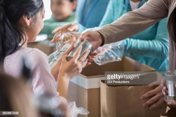 woman receives food from local food bank - canned food stock pictures, royalty-free photos & images