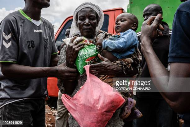 A woman receives food items during a food distribution by Team Pangaj a Kenyan voluntary group delivering flour beans milk and juice for about 900...