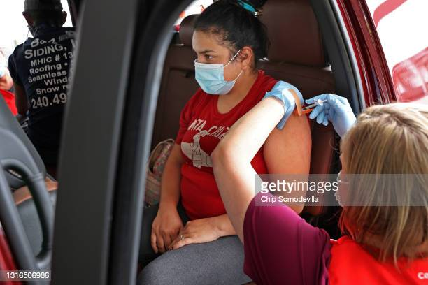 Woman receives her first dose of the Pfizer vaccine against the coronavirus from Nurse Jenni Casseday at the mass vaccination site at Ripken Baseball...