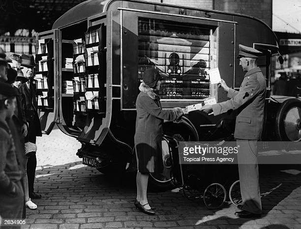 Woman receives information leaflets about holidays from a publicity van belonging to the London Midland and Scottish Railway Company, Blackpool.