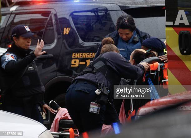 Woman receives medical assistance on the scene where active shooting is happening in Jersey City on December 10, 2019. - One officer was shot when...