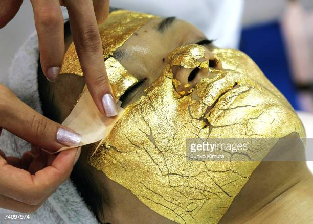 A woman receives Umo Inc's 'Gold Facial Treatment' as she is covered with sheets of 24carat gold said to be effective for antiaging care during the...