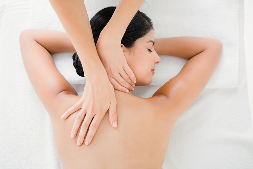 Woman receiving a back massage 667417182