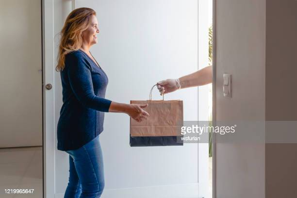 a woman receiving a bag with food on the door of her home. - receiving stock pictures, royalty-free photos & images