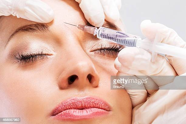 a woman receiving a botox injection in the forehead  - botox stock pictures, royalty-free photos & images