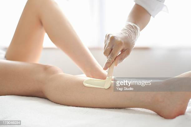 woman receiving a brazilian wax hair removal - frau gespreizte beine stock-fotos und bilder
