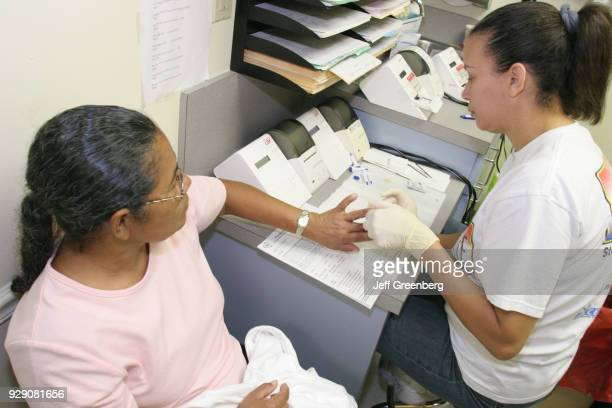 A woman receiving a free cholesterol test at the Miami Beach Community Health Center
