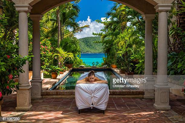 woman receiving a massage at a beautiful villa in caribbean - tourist resort stock pictures, royalty-free photos & images