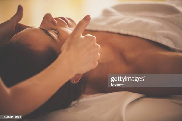 woman receiving a relaxing head massage at spa - reflexology stock pictures, royalty-free photos & images