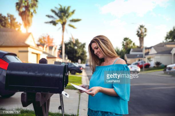 woman receiving and checking mailbox in the morning our of her house - mailbox stock pictures, royalty-free photos & images