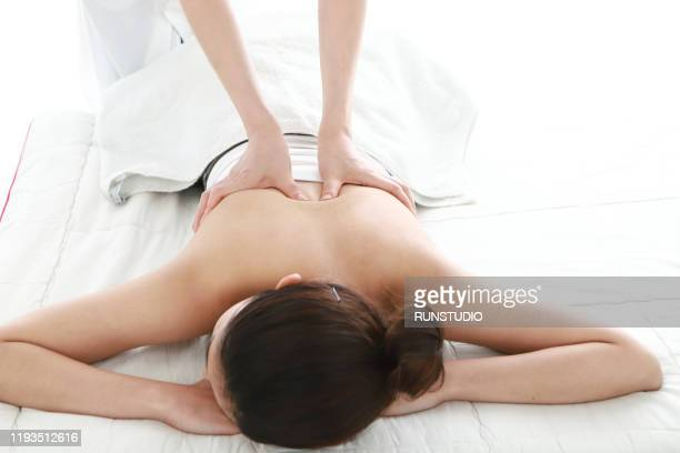woman receiving back massage - body massage japan stock pictures, royalty-free photos & images