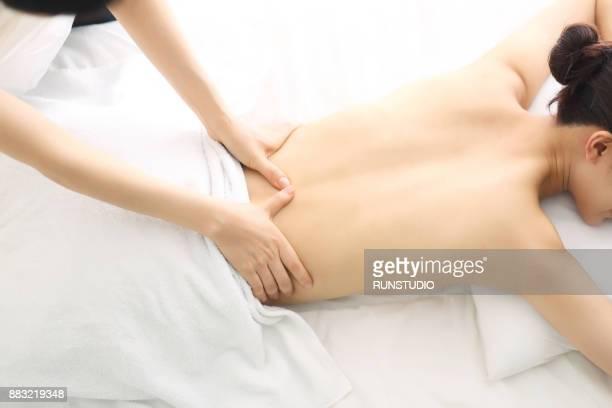 woman receiving back massage - schönheitssalon stock-fotos und bilder