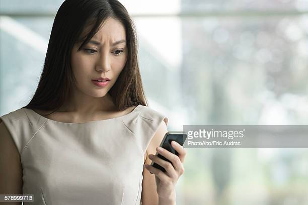 Woman receiving bad news on smartphone