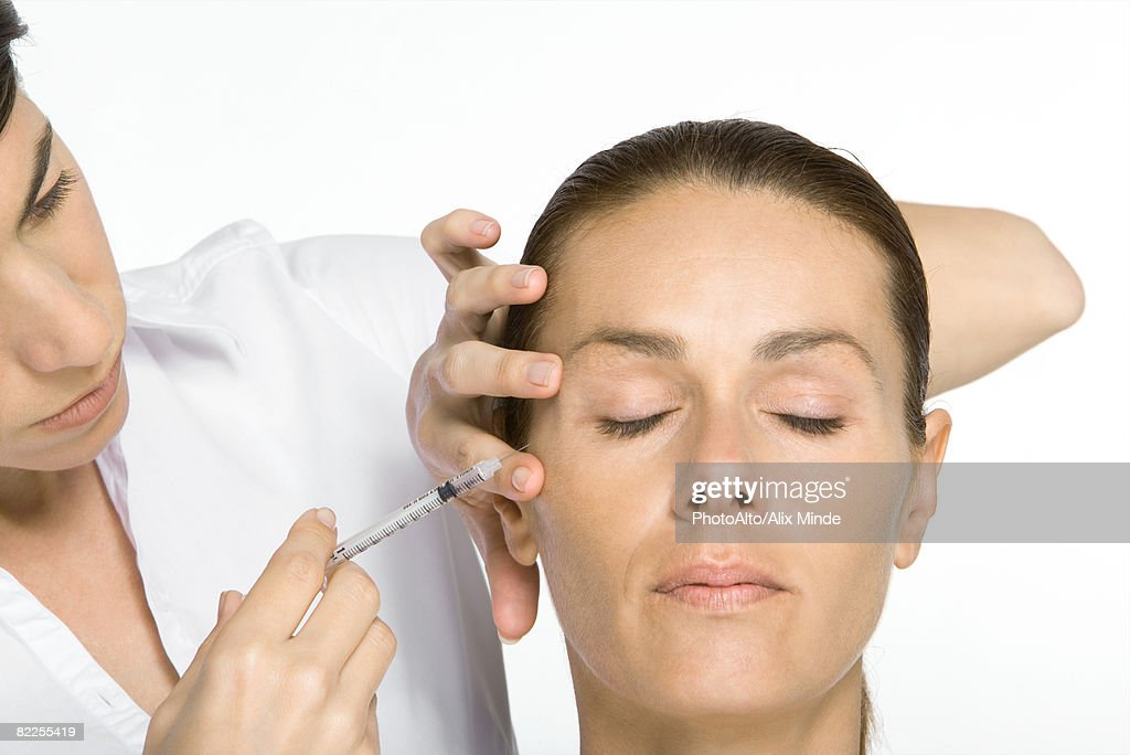 Woman receiving Botox injection, eyes closed : Stock Photo