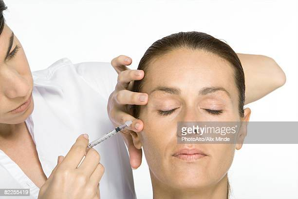 Woman receiving Botox injection, eyes closed