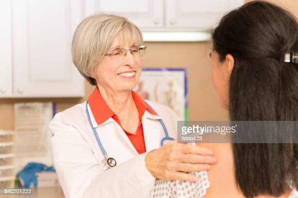 Woman receiving breast exam, mammogram at doctor's office or hospital.
