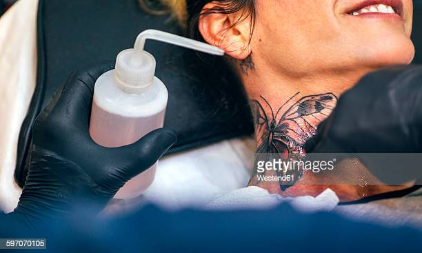 Woman receiving butterfly tattoo at her neck