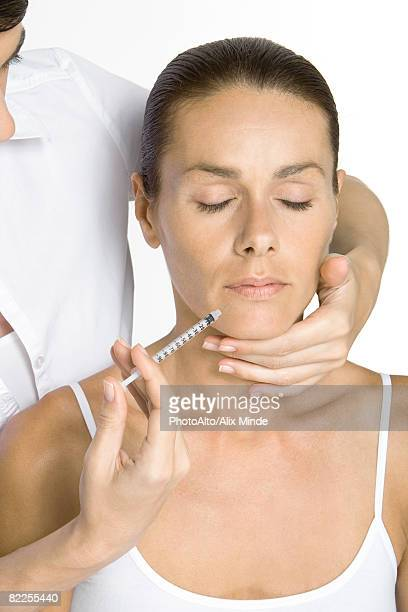 Woman receiving collagen injection, eyes closed