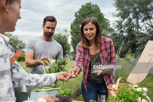 Woman receiving credit card from female customer at vegetable garden