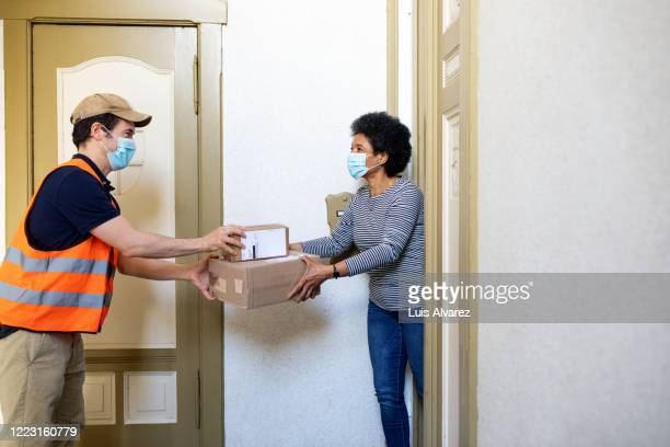woman receiving delivery box from courier during self isolation - verkehrswesen stock-fotos und bilder