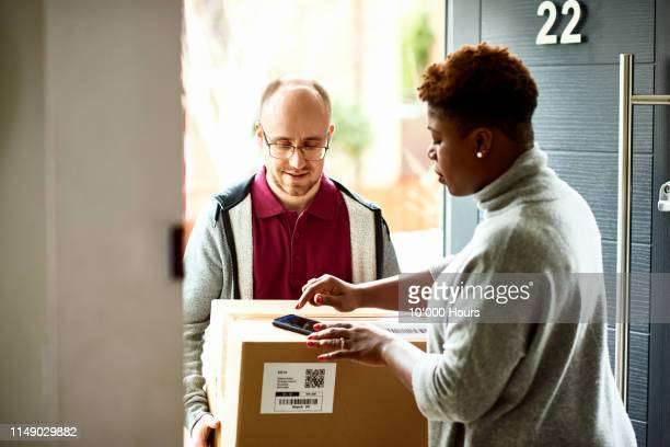 Woman receiving delivery of parcel and electronically signing