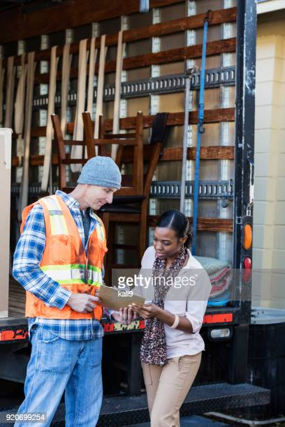 woman receiving delivery, signing a clipboard - loader reading stock pictures, royalty-free photos & images
