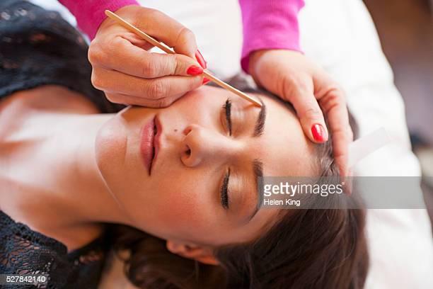 woman receiving eyebrow waxing - 眉 ストックフォトと画像