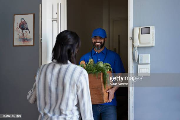 woman receiving groceries from delivery person - grocery delivery stock pictures, royalty-free photos & images