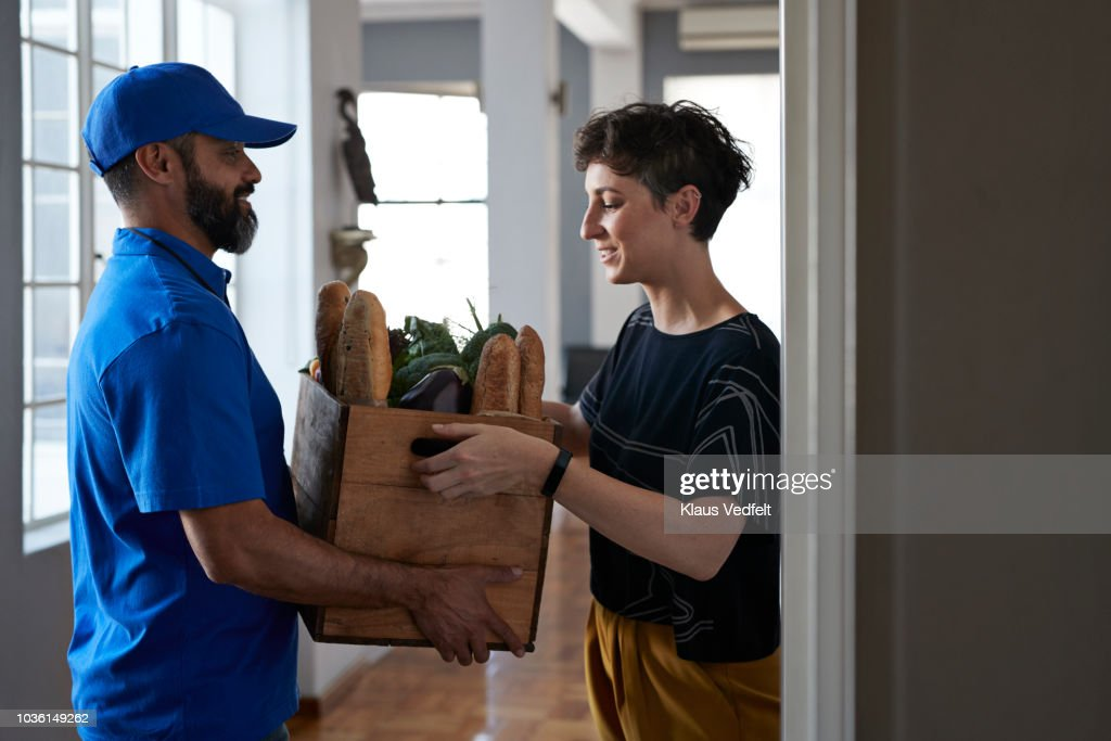 Woman receiving groceries from delivery person : Stock Photo