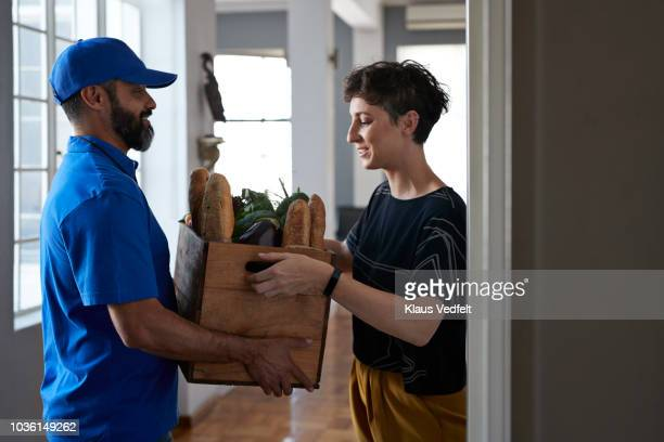 woman receiving groceries from delivery person - convenience stock photos and pictures