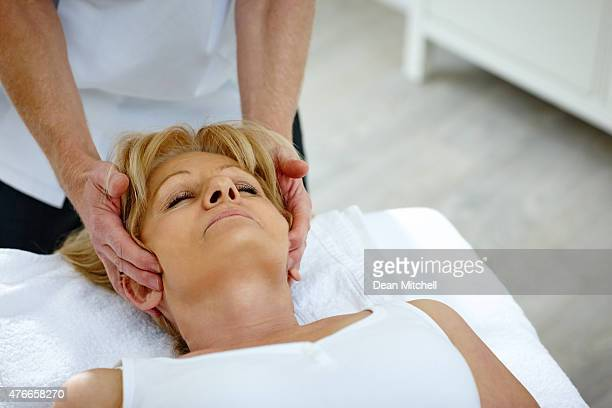 woman receiving head massage - osteopath stock photos and pictures