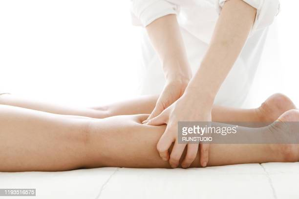woman receiving leg massage - body massage japan stock pictures, royalty-free photos & images