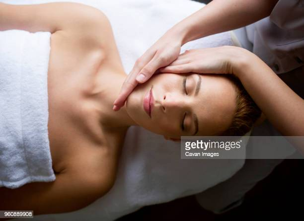 woman receiving massage from female therapist in spa - massaggi foto e immagini stock