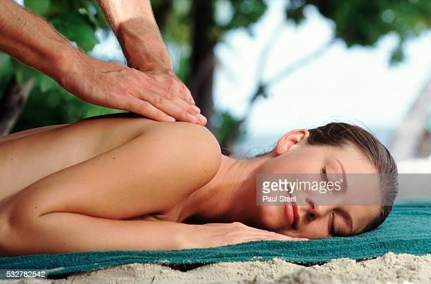 woman receiving massage on beach - erotische massage stockfoto's en -beelden